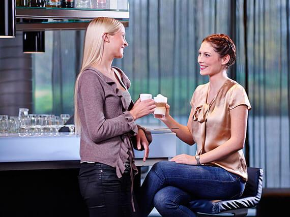 Zwei Frauen trinken Kaffeespezialität aus einer Melitta Gastronomie Kaffeemaschine